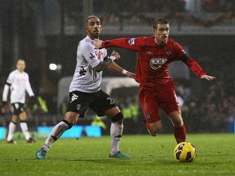 Steven Davis battles in the rain with Fulham's Ashkan Dejagah